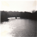 Black and white photo of bridge across lake