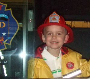 A smiling young boy with a firefighter helmet and jacket on