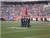 Honor Guard members walking with flags out to the fifty yard line