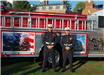 Two fire fighters pose at attention in front of memorial fire truck