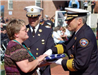 Woman collects folded memorial flag from fire fighter
