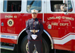 Fire fighter poses in front of Loveland-Symmes Fire Department Engine 62 truck