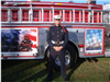 Fire fighter poses in front of memorial truck