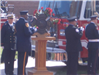 Fire fighters holding memorial flag and rose
