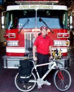 Paramedic holding a bike next to fire engine
